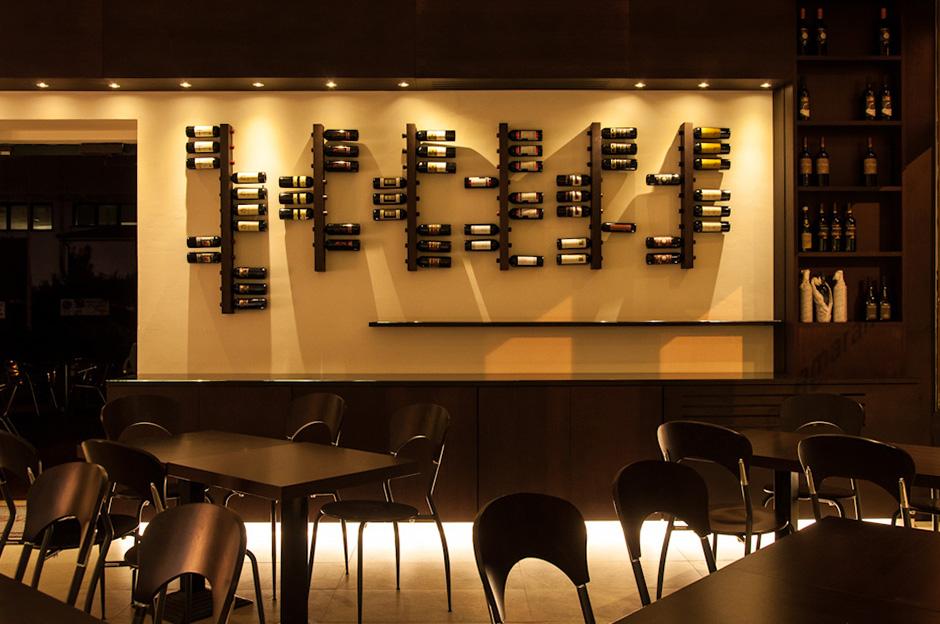 La parete con l\'esposizione di vini ed il banco per aperitivi